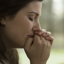 Horizontal view of depressed young woman crying